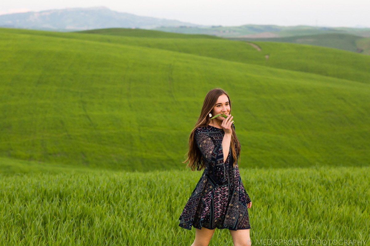 young girl walking through a green field in Tuscany