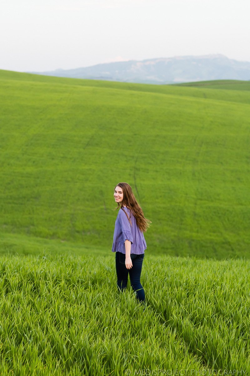 teenage girl walking through a green field in Tuscany