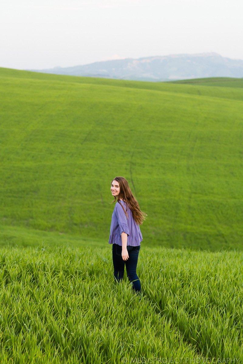 teenage girl walking through a green field in Tuscany
