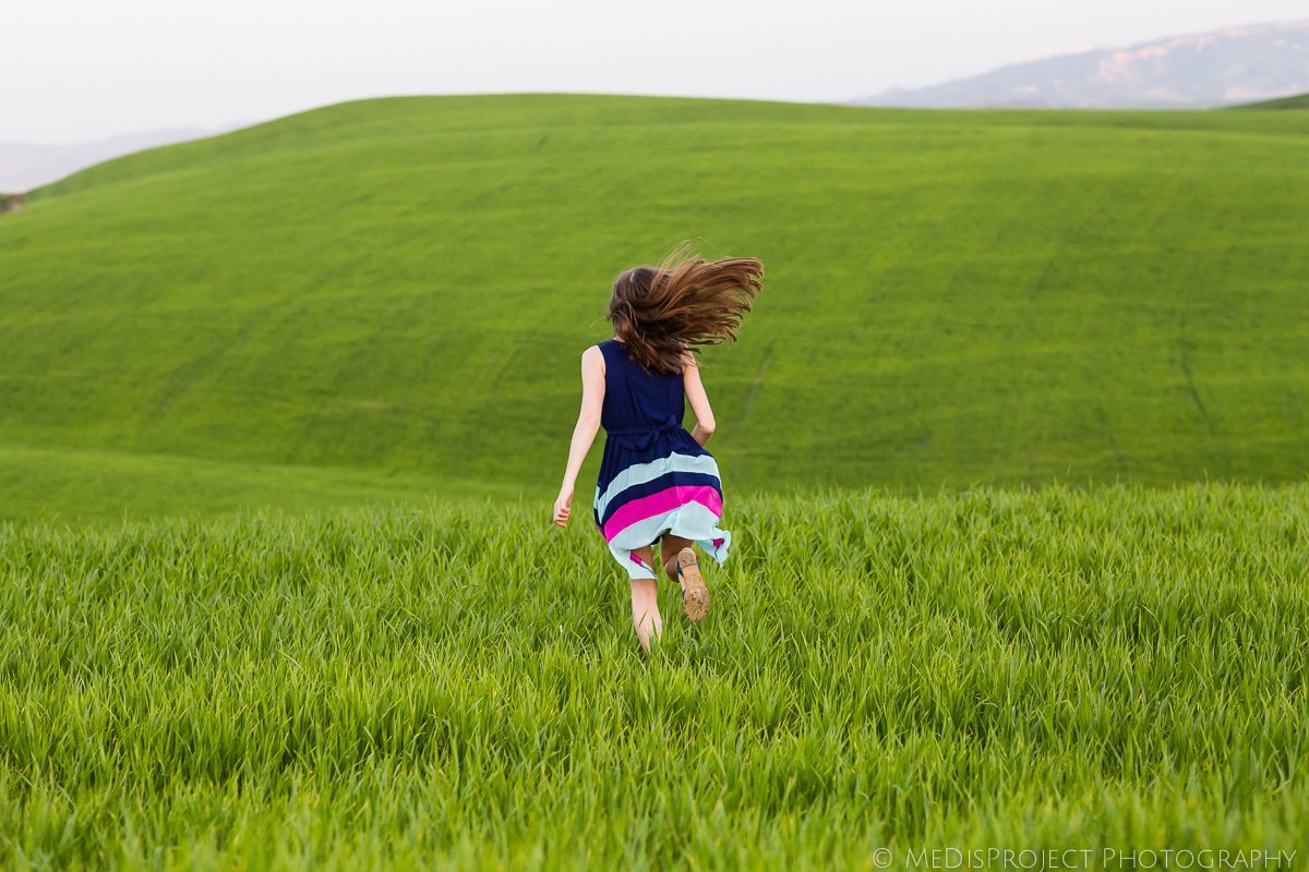 young girl running through a green field in Tuscany