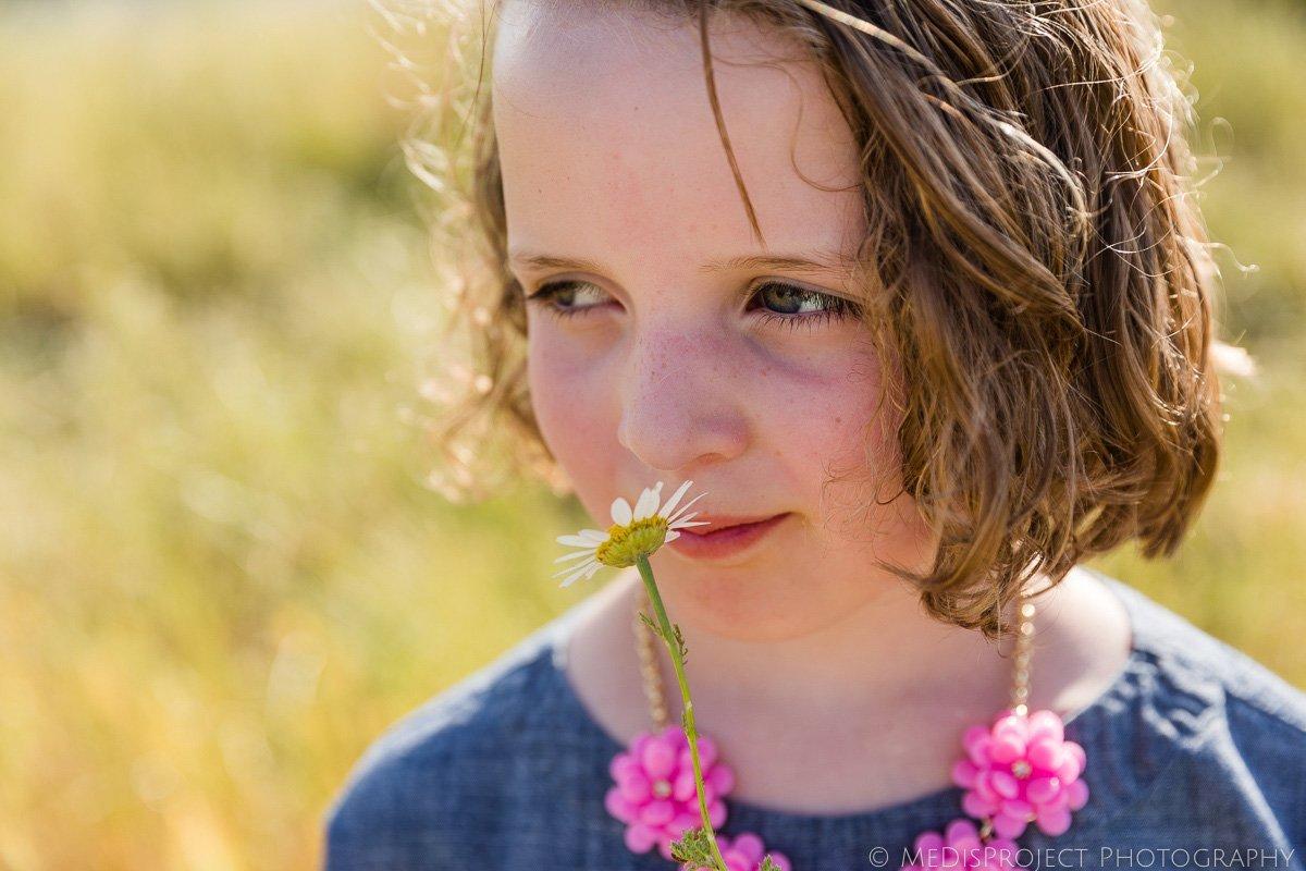 girl smelling daisy flower