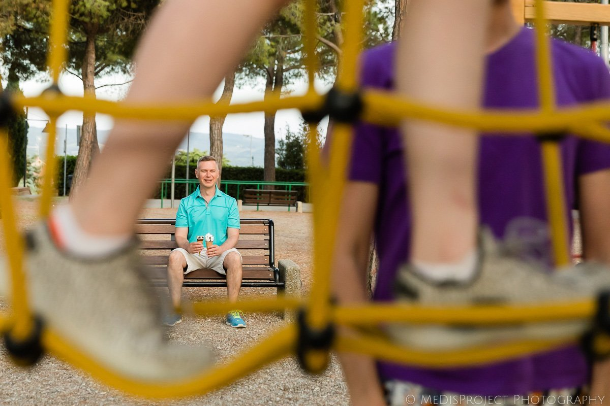 daddy waits for his daughters with two ice creams in a playground