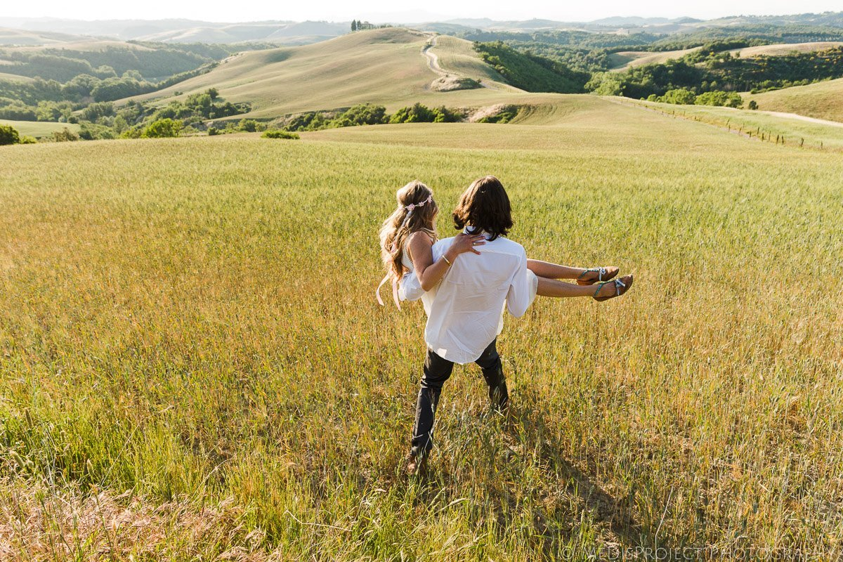 Boho style couple taking wedding photos in the barley fields