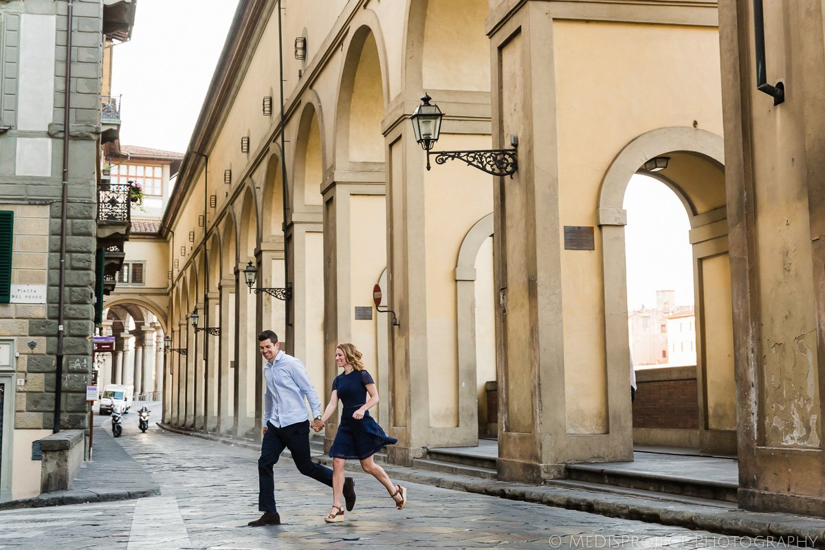 a couple running across the street in Florence oldtown