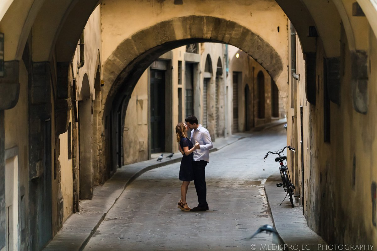 a couple kissing under the bow in Florence