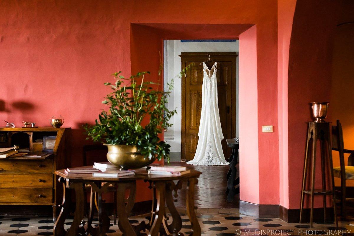 Martina Liana wedding gown hanging to the door