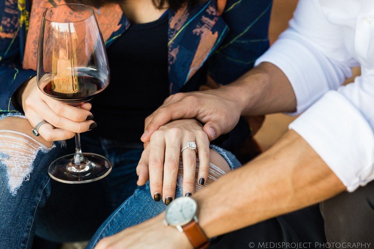engagement ring and red wine glass