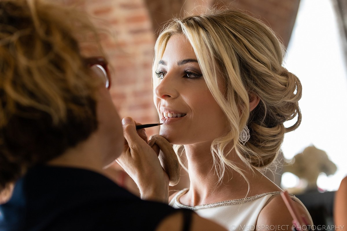MUA working on the bride before the wedding ceremony