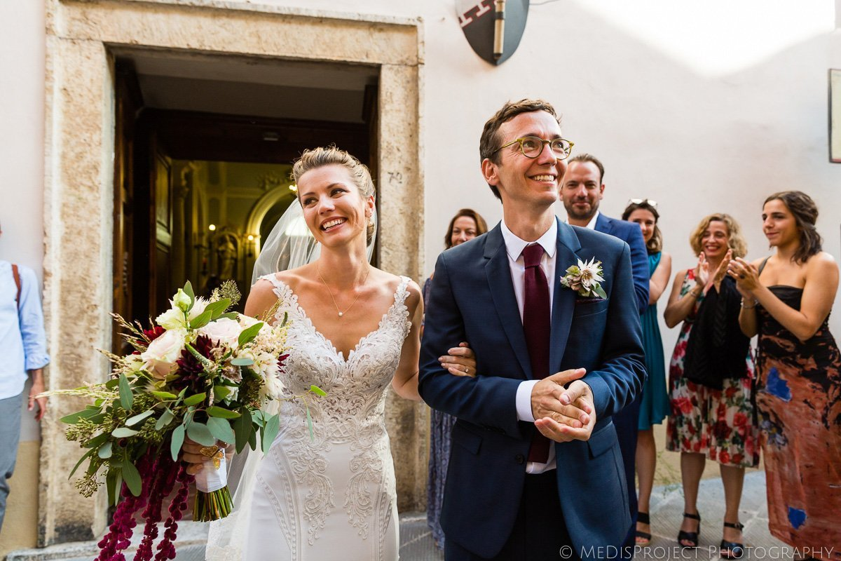 bride and groom exit the church after wedding ceremony in Italy