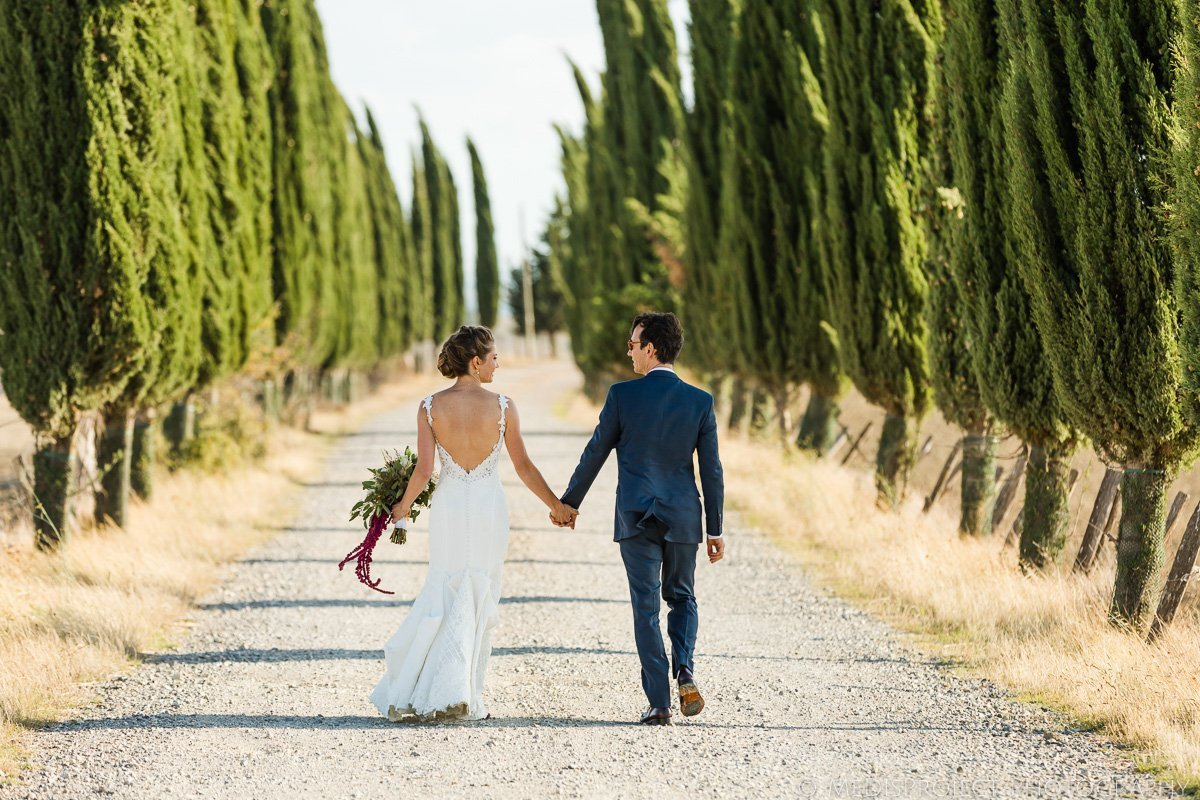 hand in hand in a typical cypress boulevard in Tuscany