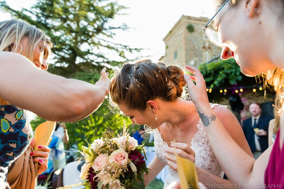 guests helping the bride to remove rice from her hair