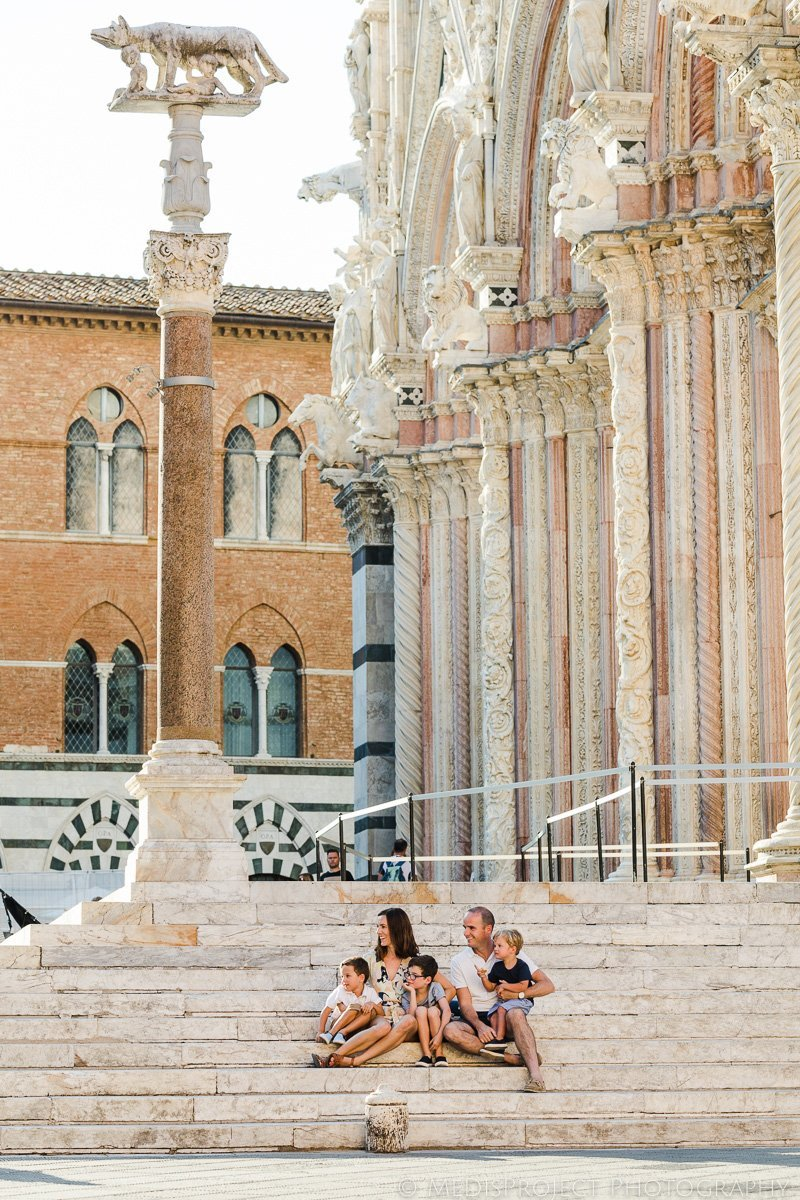 Family sitting nearby the Duomo in Siena