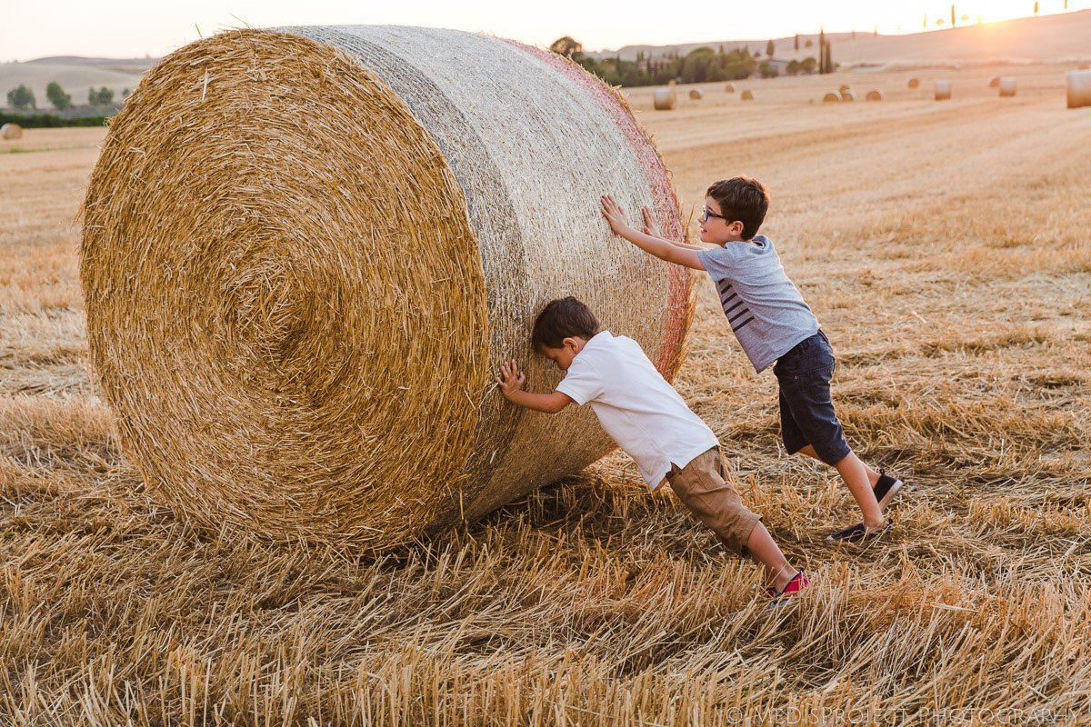 funny picture of two kids pushing a hay bale