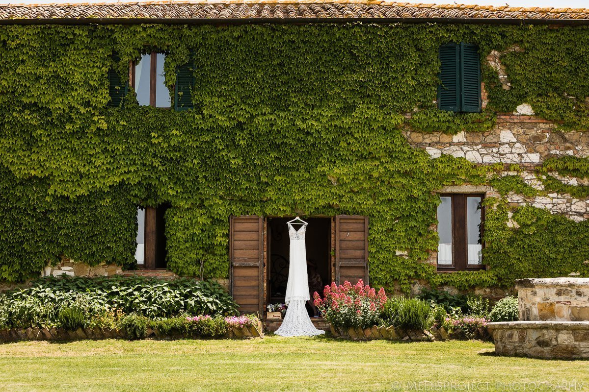 A white wedding gown hanging outside Agriturismo il Rigo