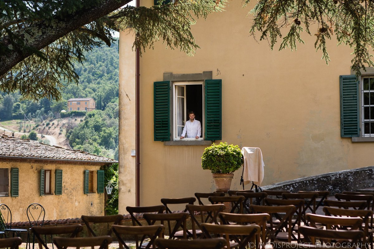 the groom looking out of the window from his room in Villa Petrolo