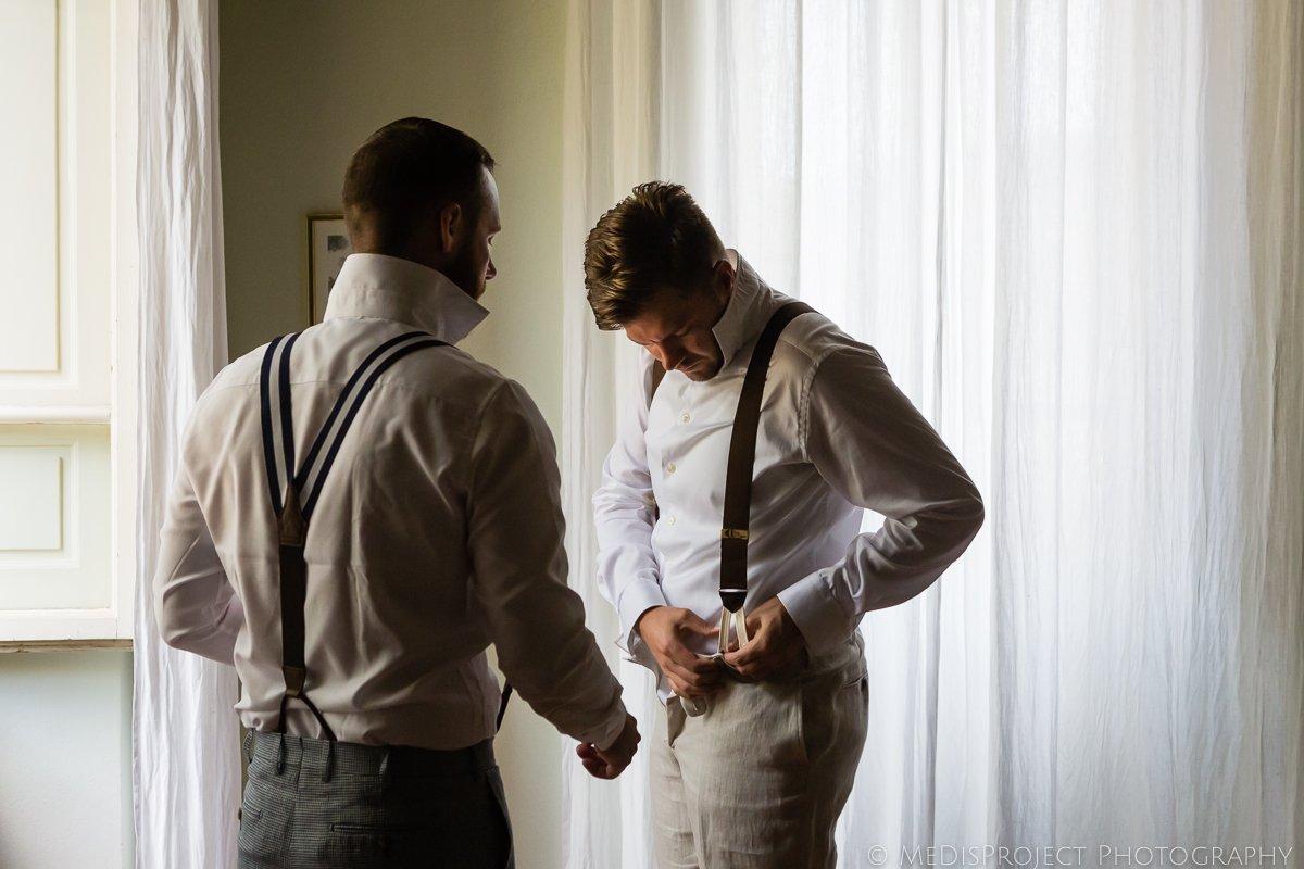 Groom and groomsman wearing suspenders