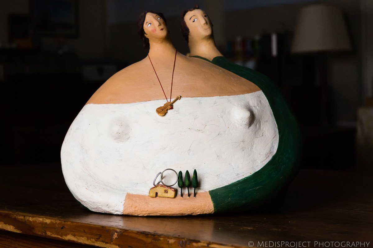Wedding rings on a paper-mâché statue representing a couple hugging