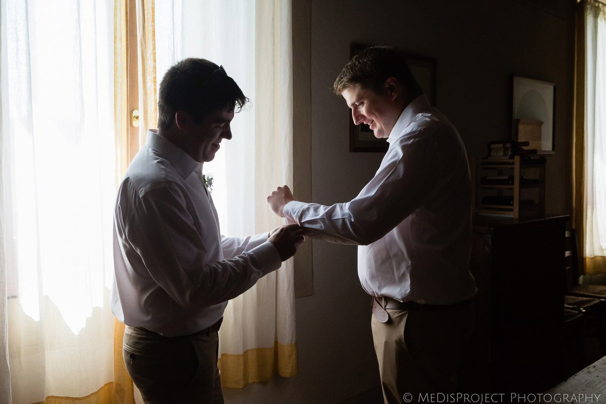best man helps groom put cufflinks