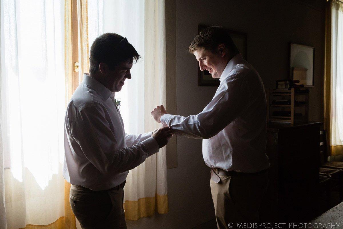 best man helps groom put cufflinks