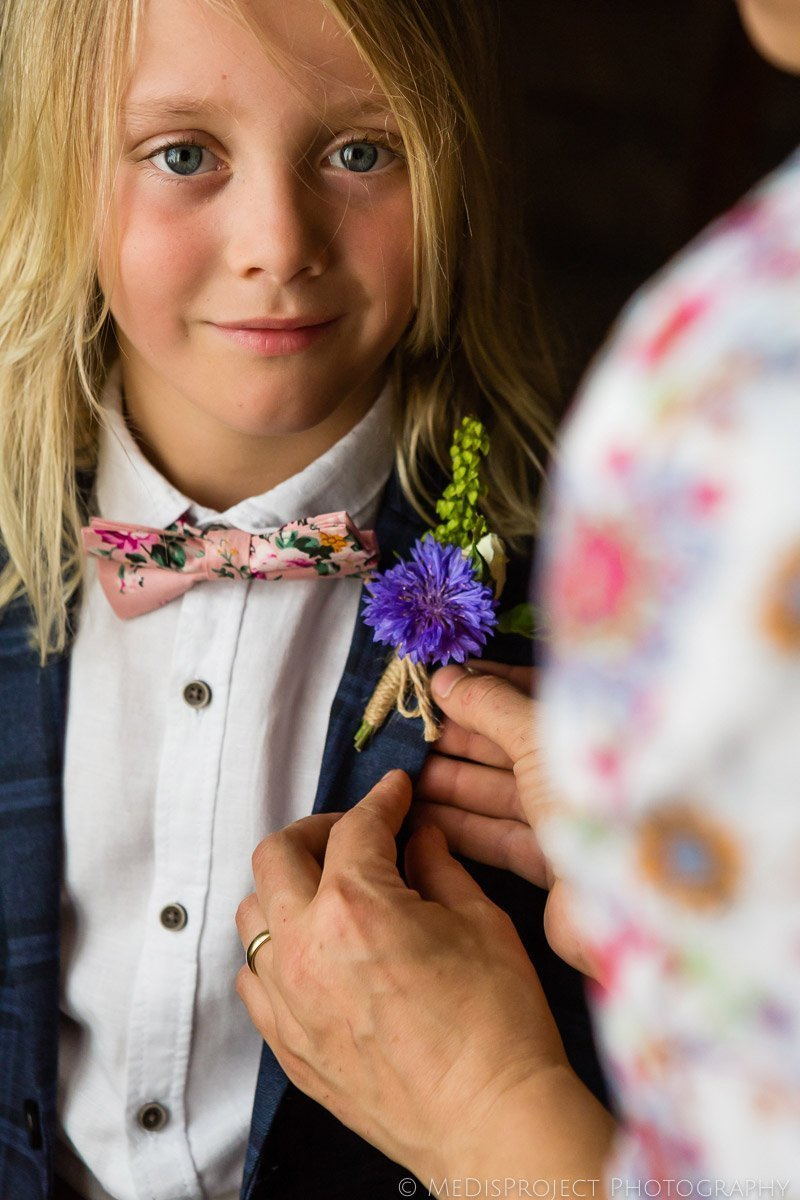 lady puts a violet buottonniere on a young boy before a wedding at Il Rigo