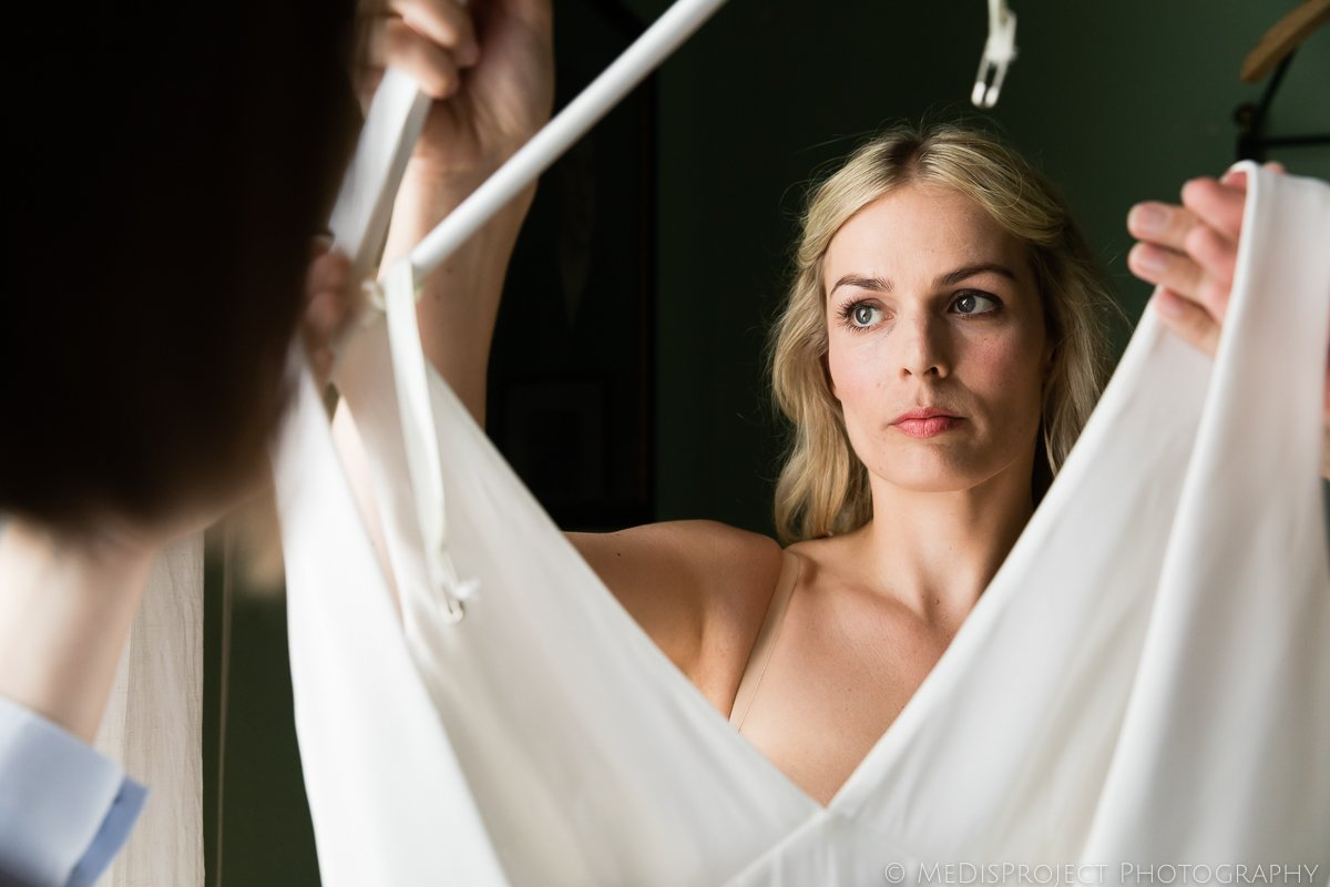 Beautiful blonde Danish bride preparing to wear her wedding gown