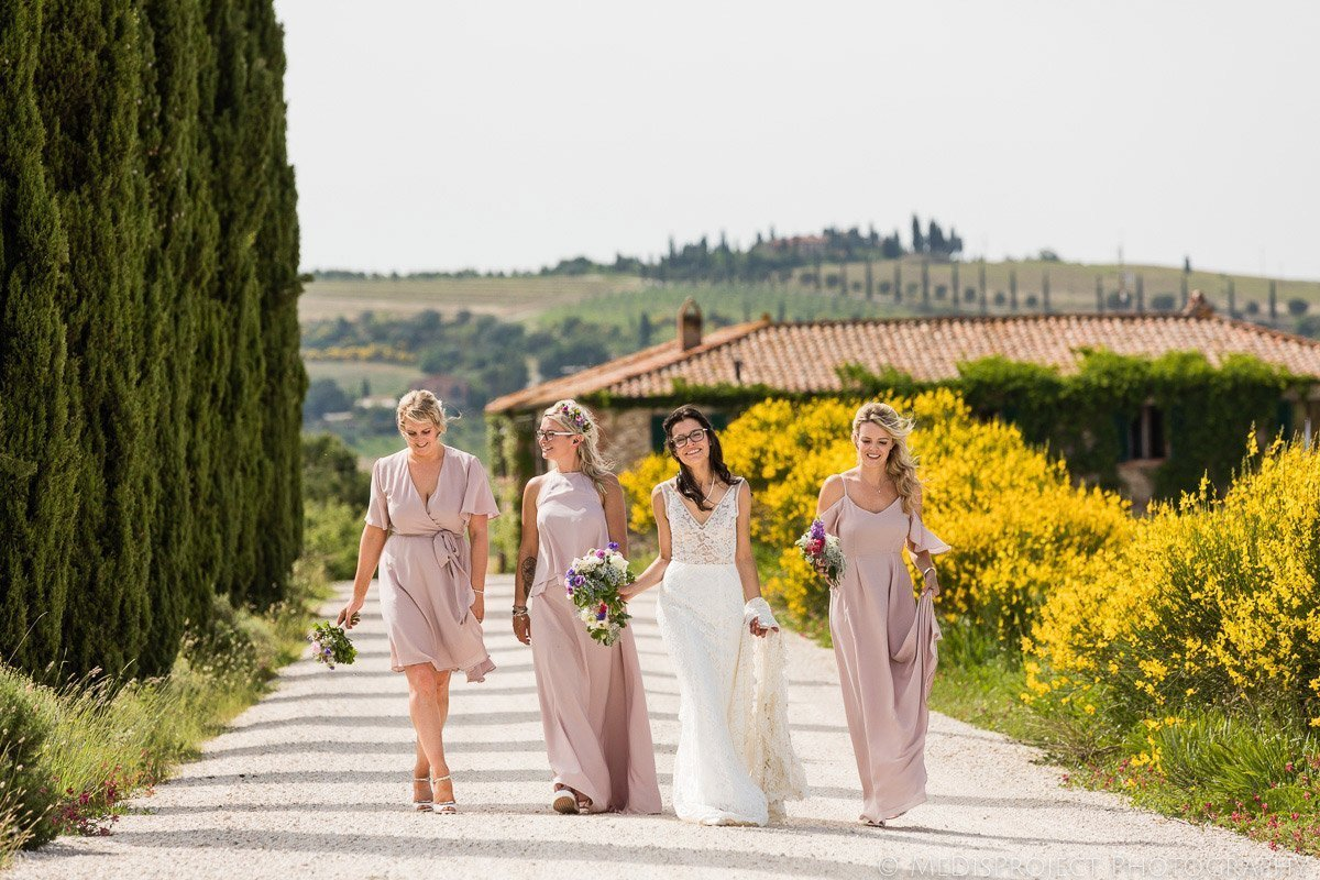 Bride and bridesmaids walking along yellow flowers and cypresses in front of Agriturismo il Rigo