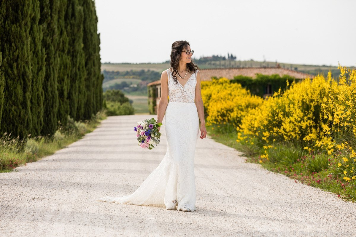 the bride walking along yellow flowers and cypresses in front of Agriturismo il Rigo