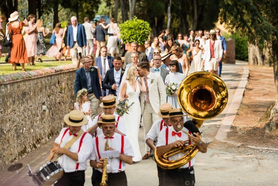 Folk Italian street band leads the wedding party to reception