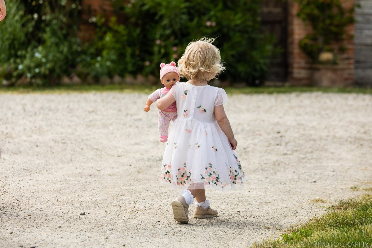 a little girl and her dolly during a wedding reception at Il Rigo