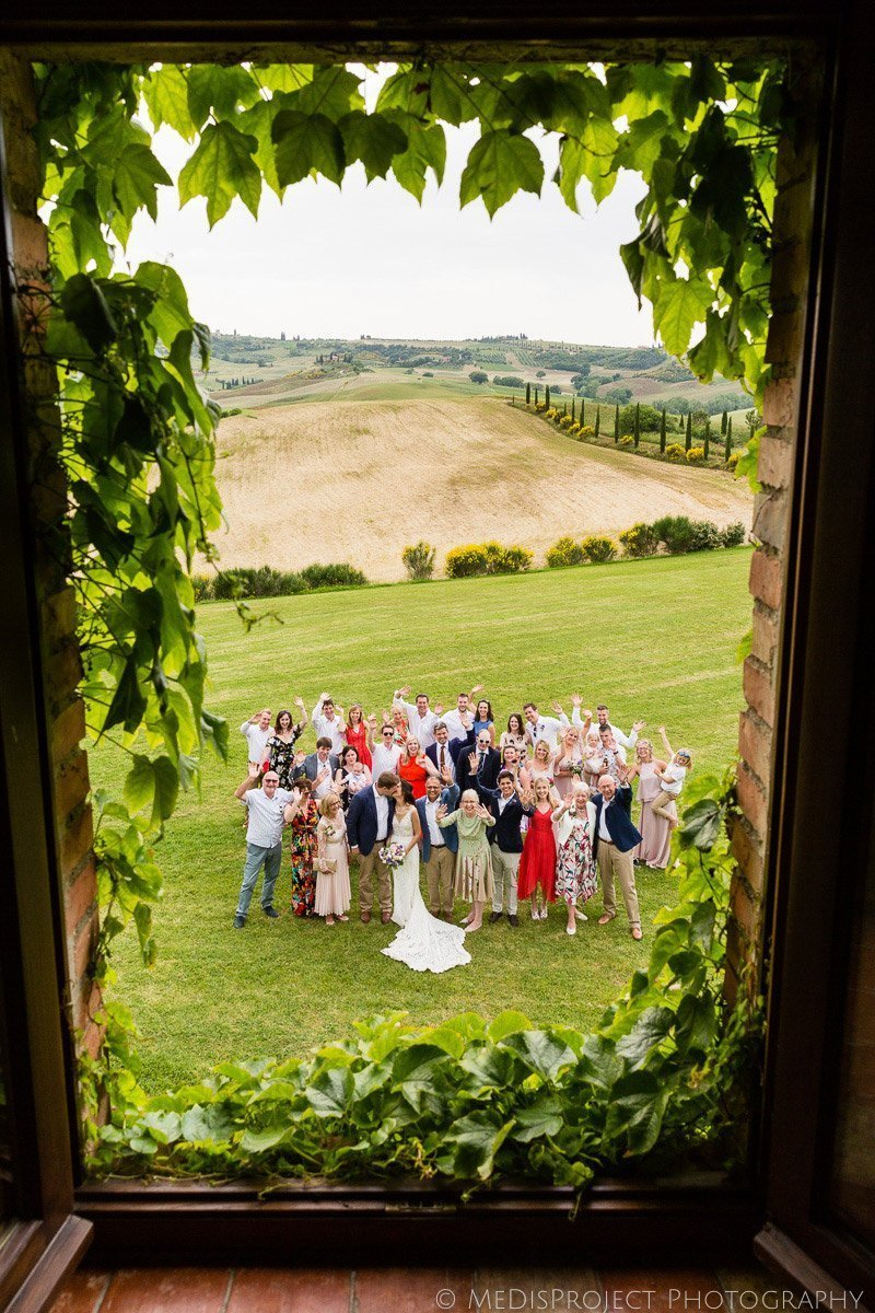 Wedding large group photo from a window at Agriturismo il Rigo