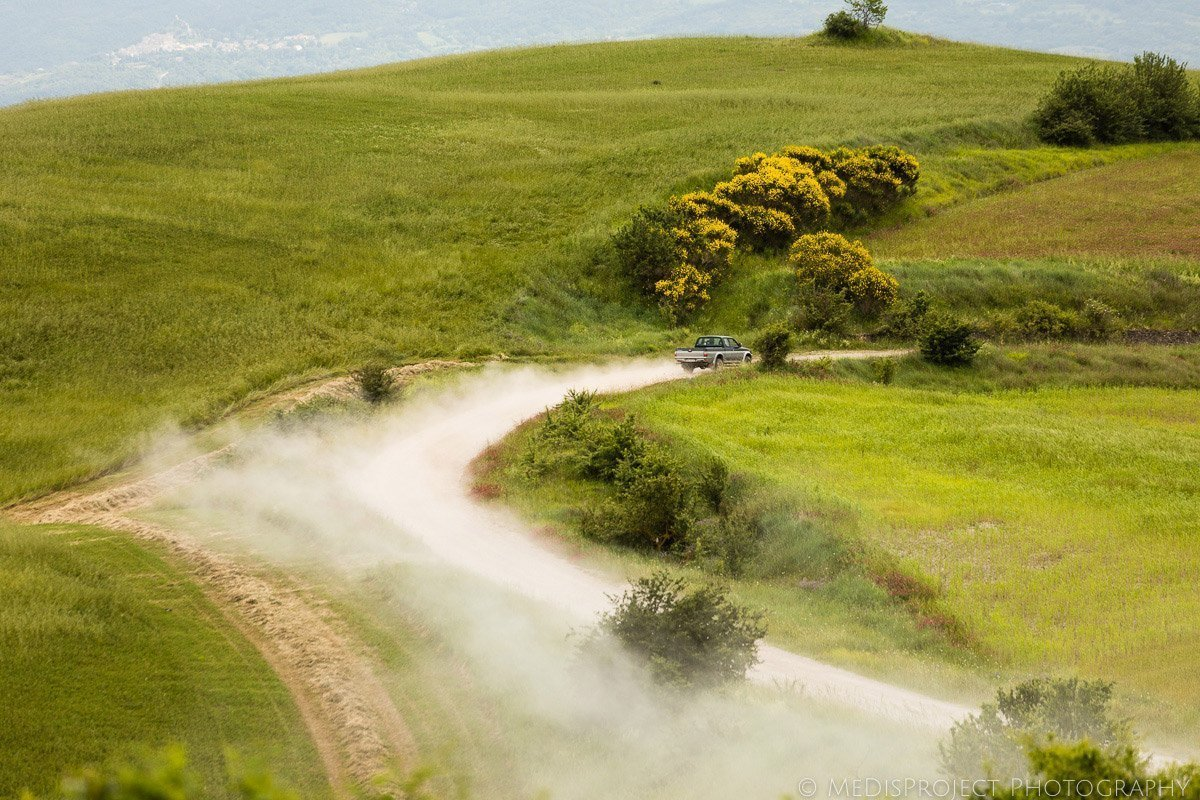 a car drives through a dusty country road in Val d'Orcia Tuscany
