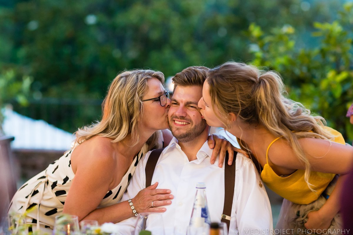 Female guests kiss the groom during wedding dinner