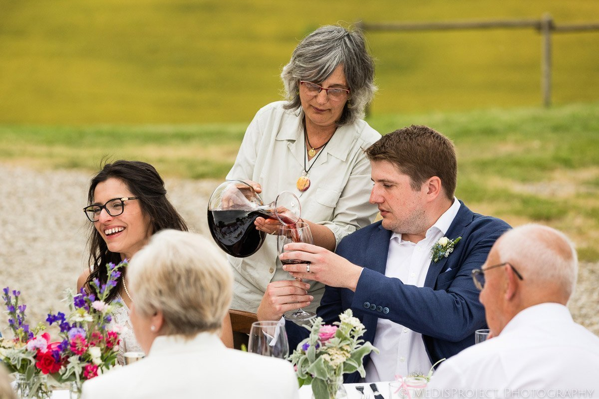 Agriturismo il Rigo's landlady serving the wine to the bride and groom