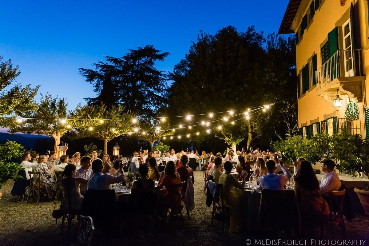 Fairy light and blue sky during a wedding dinner at Villa Petrolo