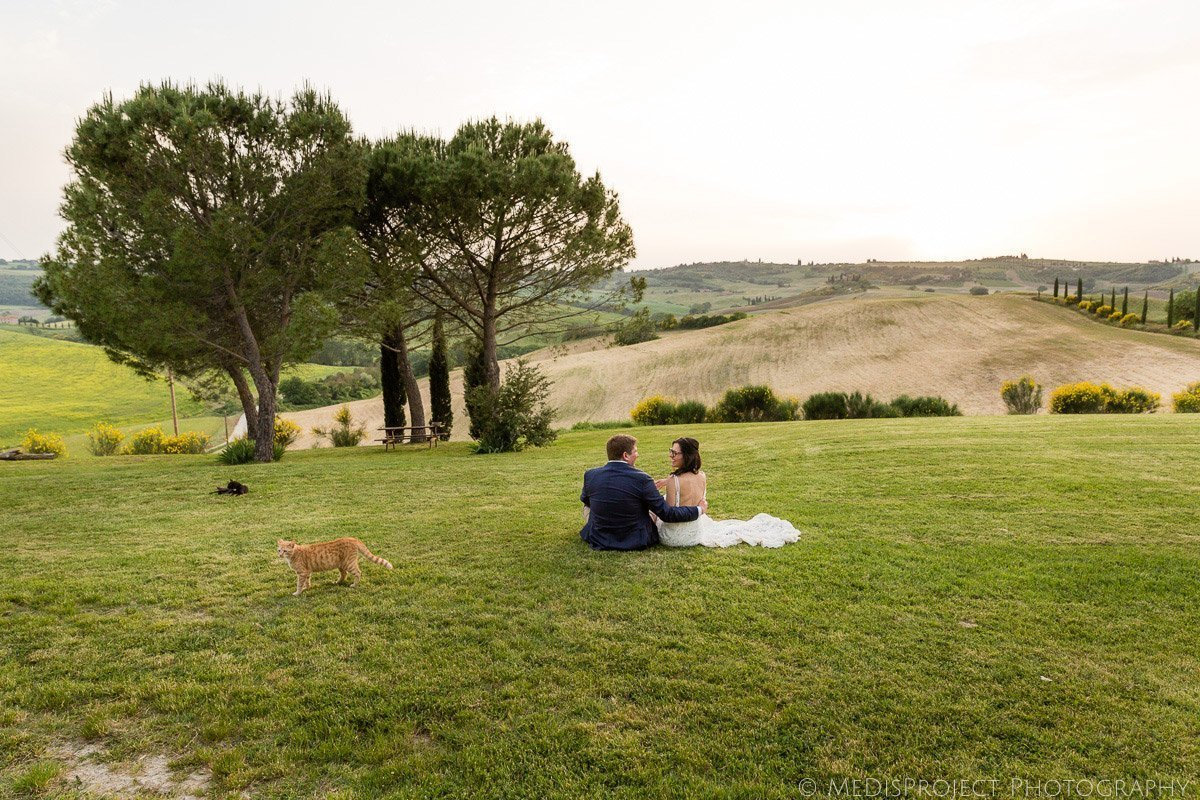 bride and groom sit on the grass at sunset