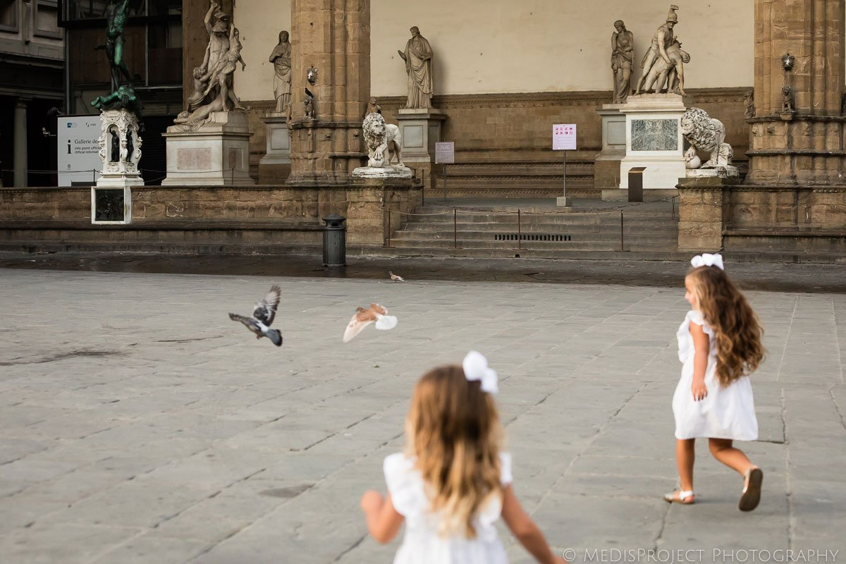 kids chasing the pigeons in the city center of Florence