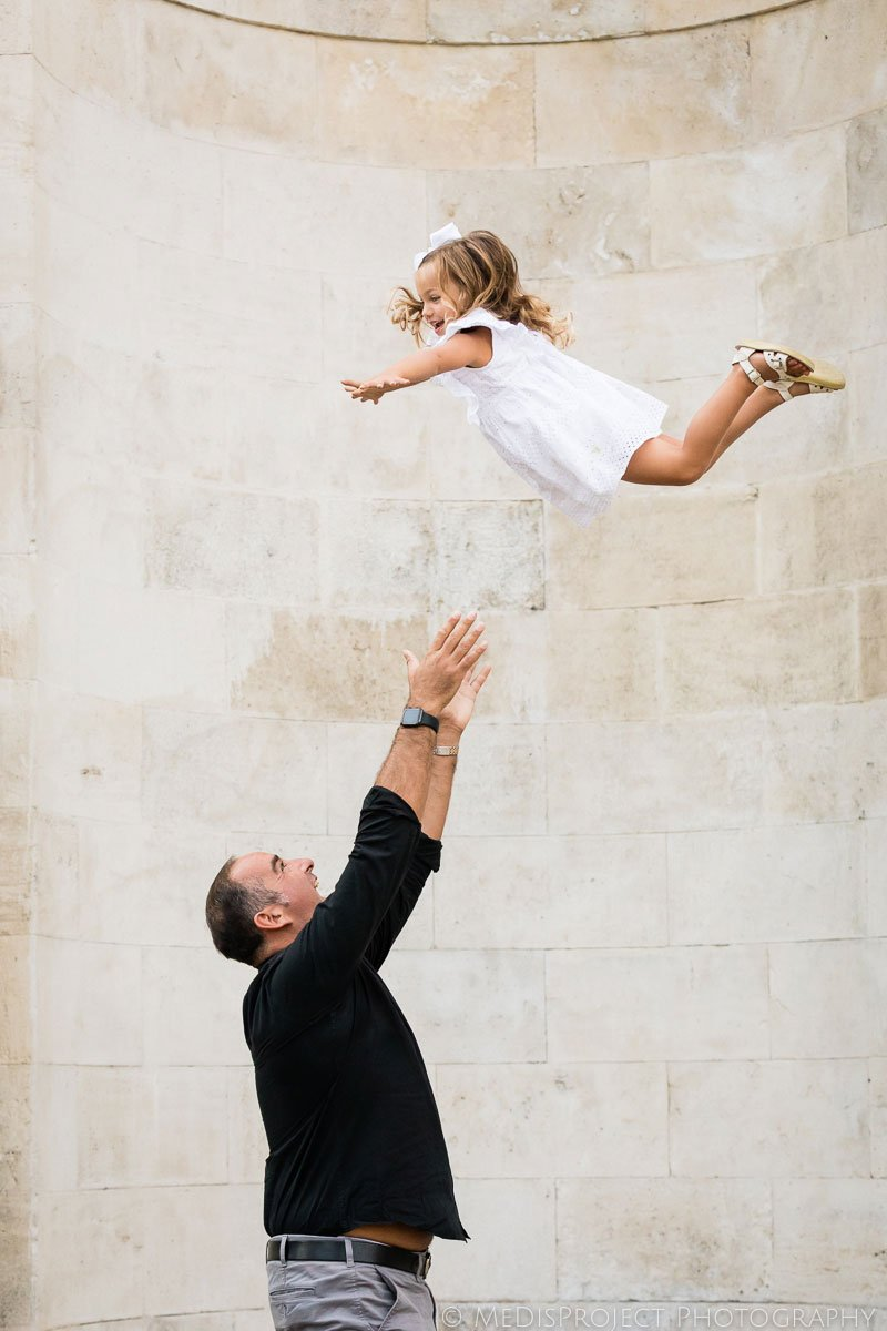 father throwing baby in air during the photo session in Florence