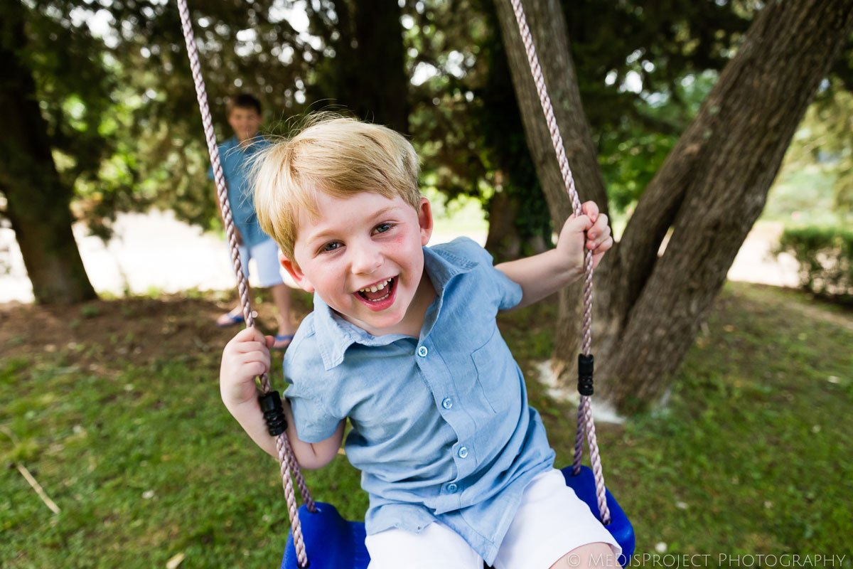 kid playing on a tree swing during a family photoshoot