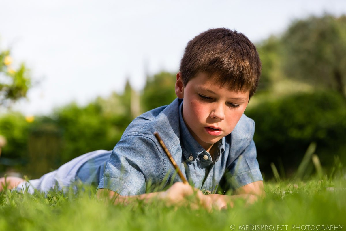boy laying on the grass and drawing with a pencil