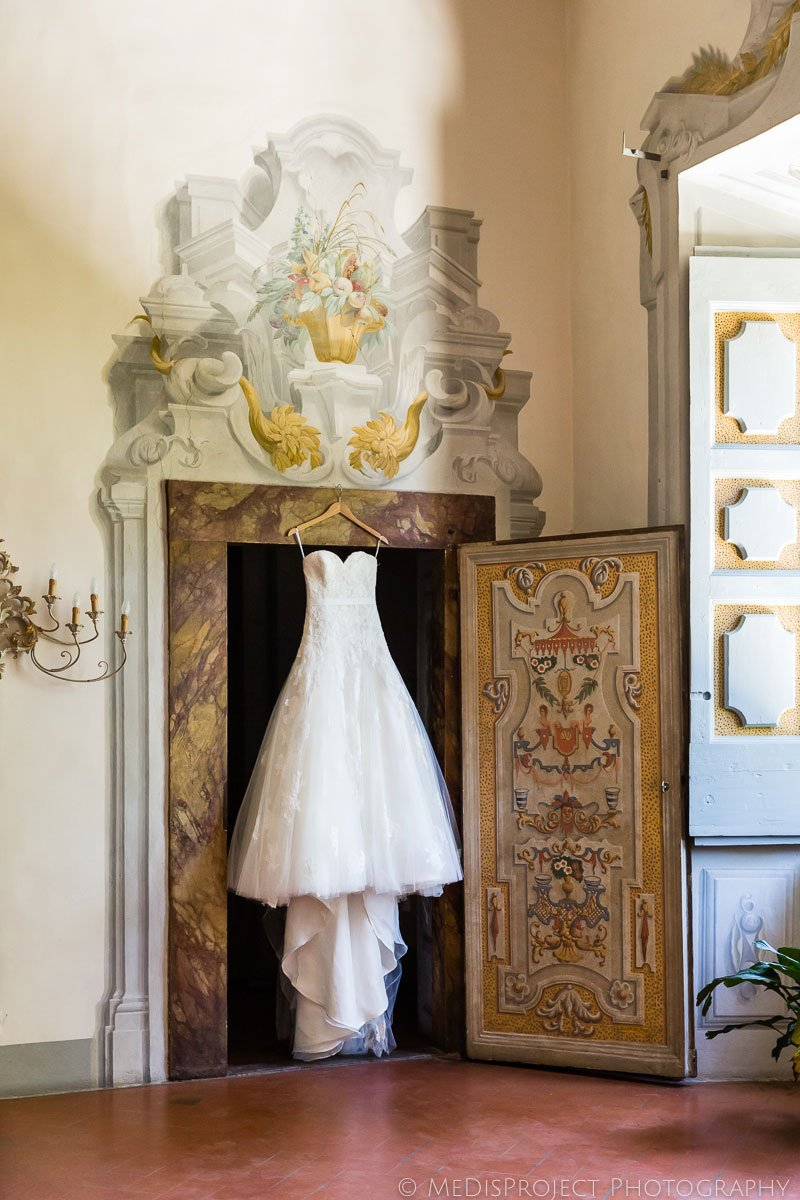 wedding gown hanging on decorated doorway at Meleto
