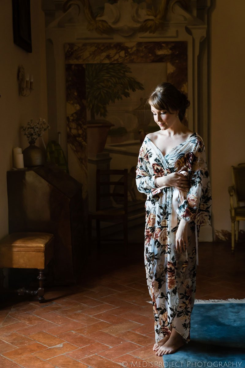 Bride wearing nightgown getting ready for wedding at Meleto Castle
