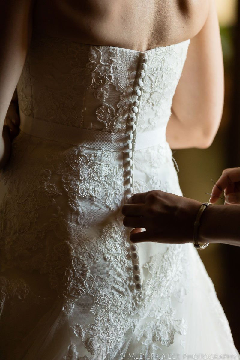 Bride closing gown while getting ready for wedding at Meleto Castle