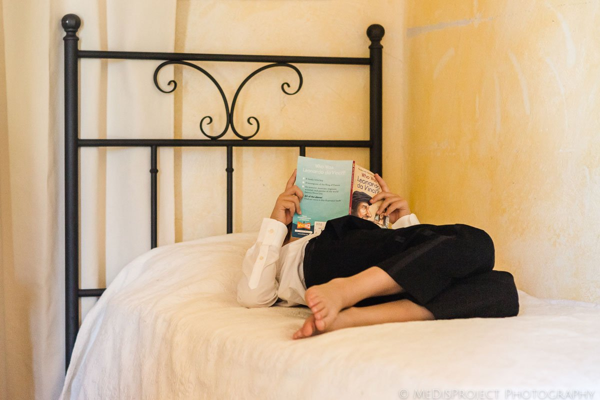 Boy in bed reading a book about Leonardo da Vinci