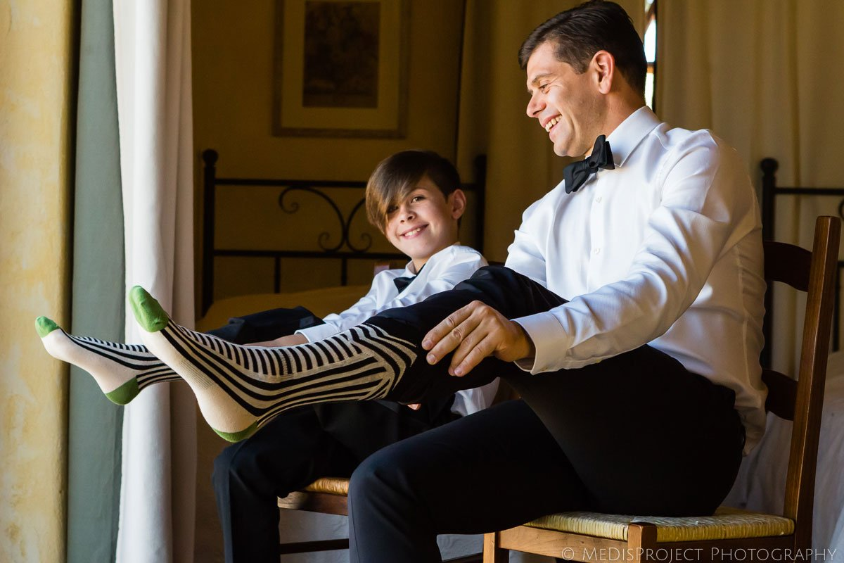 Groom and his son putting funny socks on