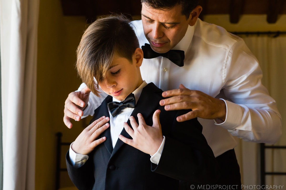 Groom and his son getting ready for wedding in Tuscany