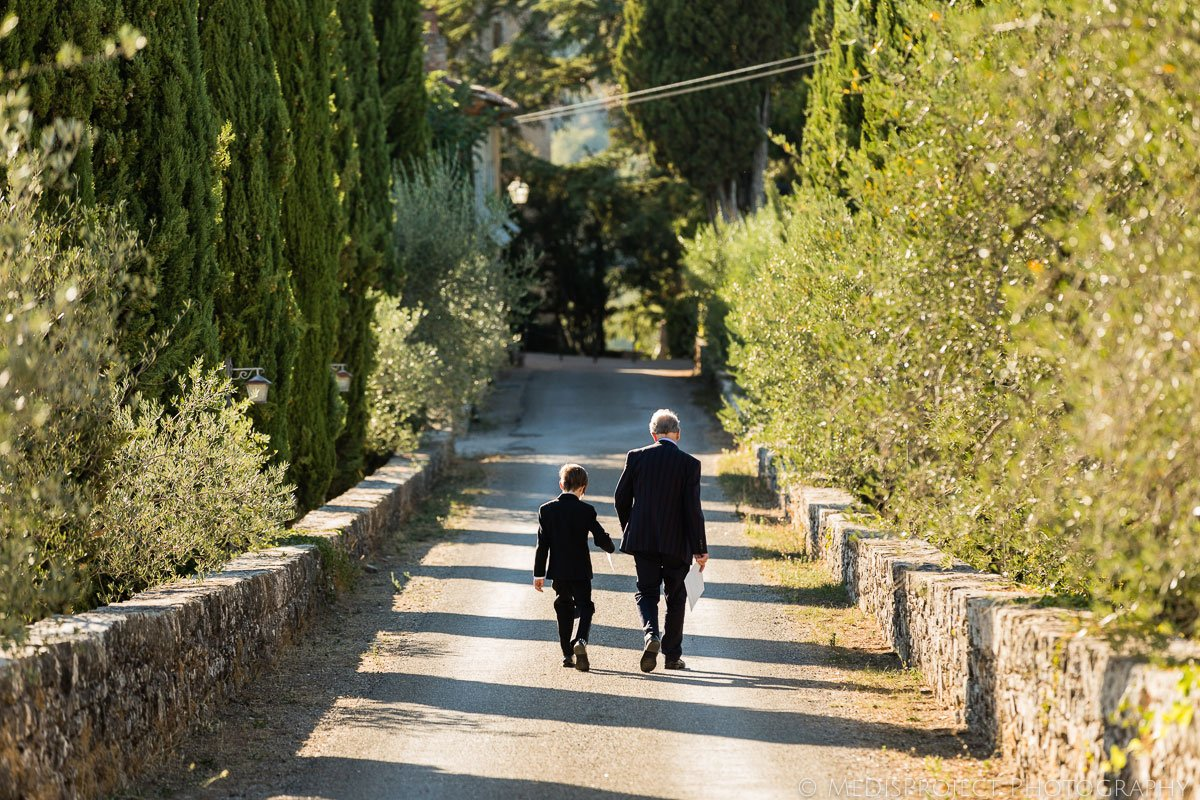 A little boy and his grandfather walking down a Tuscan country road