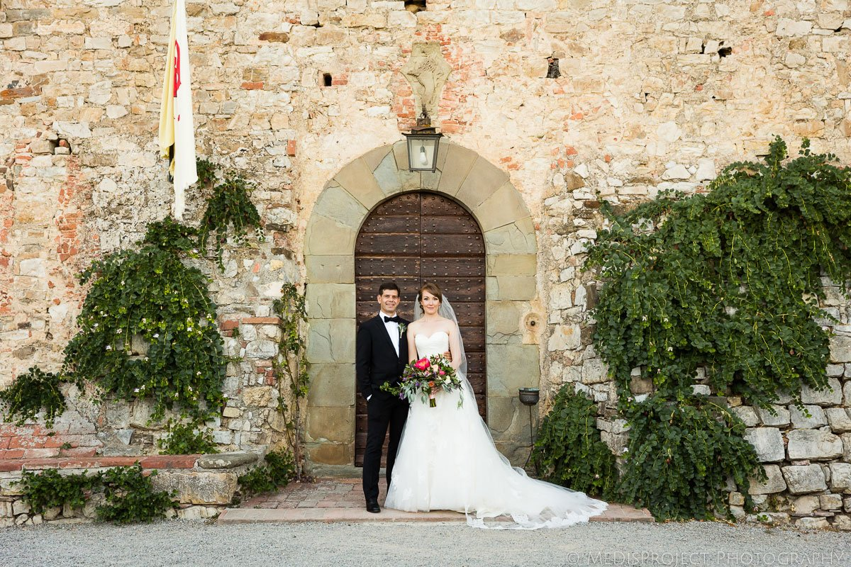 Classic wedding photo in front of a main door at Meleto Castle