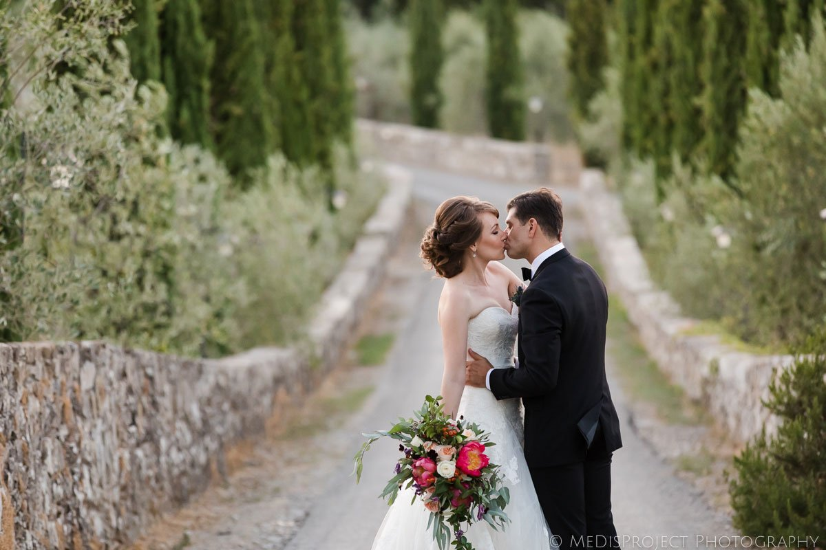 Bride and groom kissing in the middle of a country road
