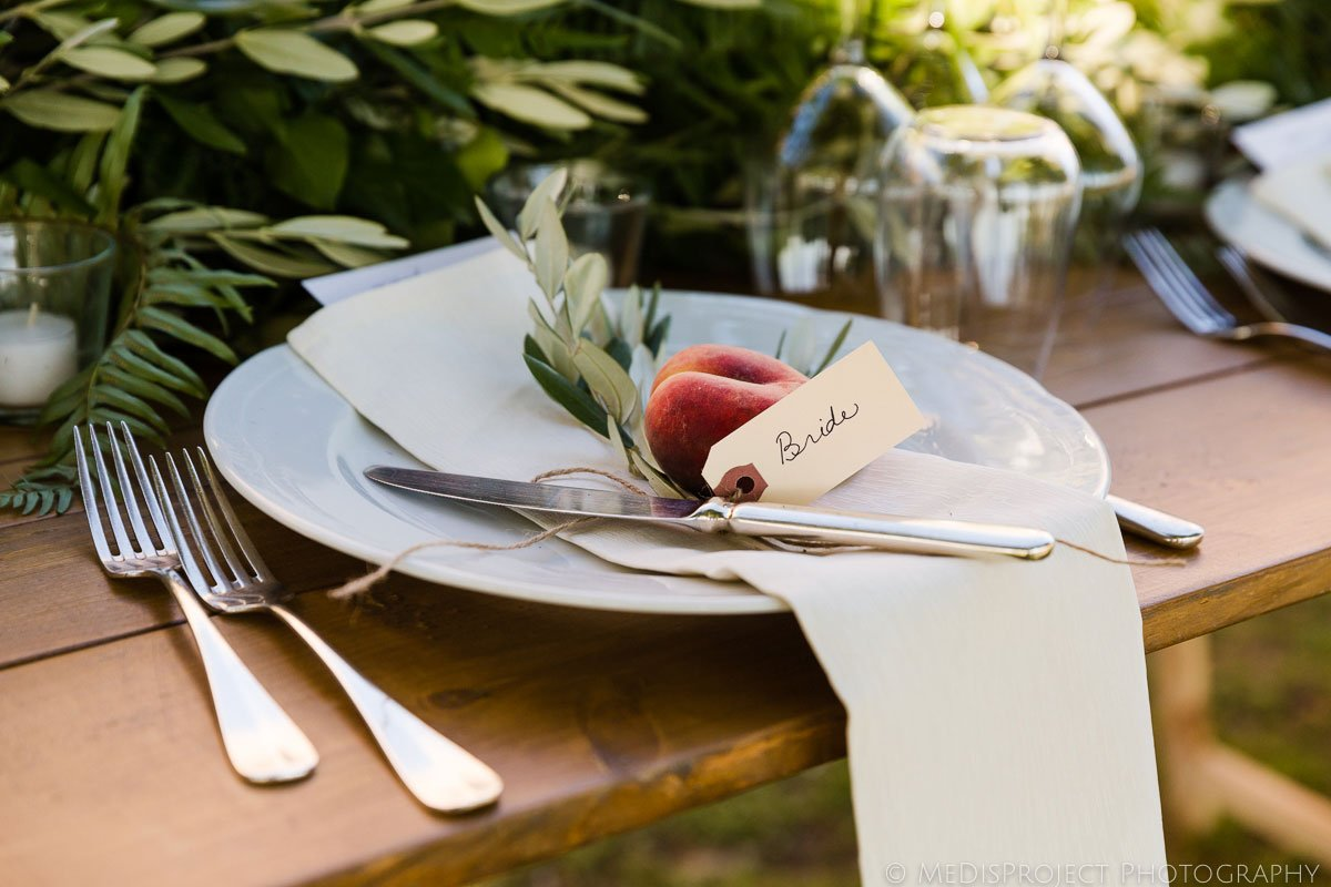 Wedding table setting with fruit and greenery