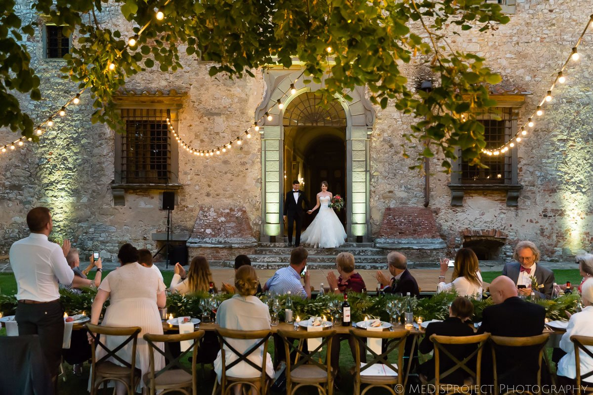 the bride and groom enter for wedding dinner at Meleto Castle